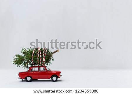 Red toy car with a christmas tree on the roof, white background, shallow depth of field. #1234553080