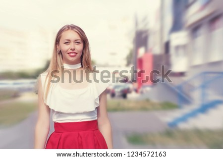 Woman with long fair hair and red lips standing on the street. Photo with blured background. Confident, positive, smiling girl dressed in white blouse. Street, shop, houses on background. #1234572163