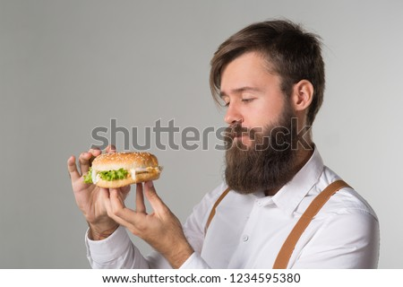 Man with beard in white shirt and suspenders eating junk food from a fast food hamburger or cheeseburger on gray background #1234595380