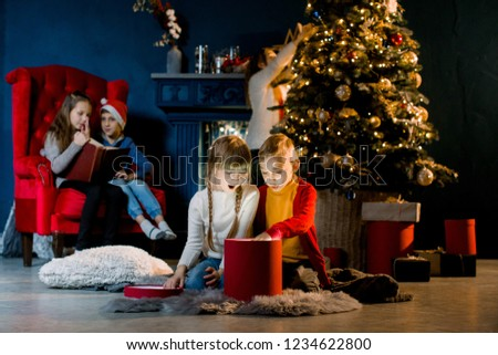 Cozy room decorated in a Christmas style. Beautiful children view a magical gift and prepare for the holiday.