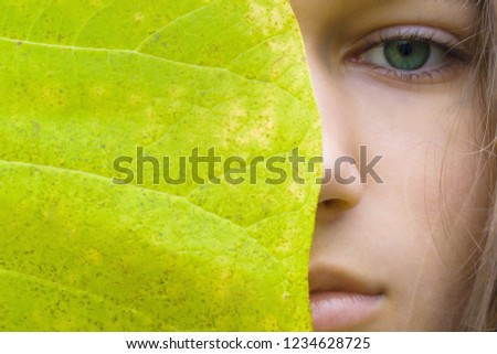 Beauty young blonde woman with green eyes without make up. Teen girl model and big green leaf. Concept of Spa, skin care, wellness, nature organic cosmetic and environmental protection. Copy space. Royalty-Free Stock Photo #1234628725