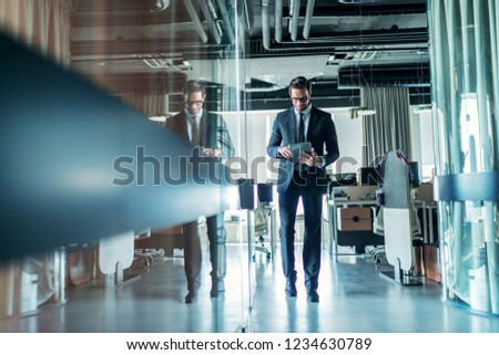 Businessman walking through company and using tablet. Full length. #1234630789