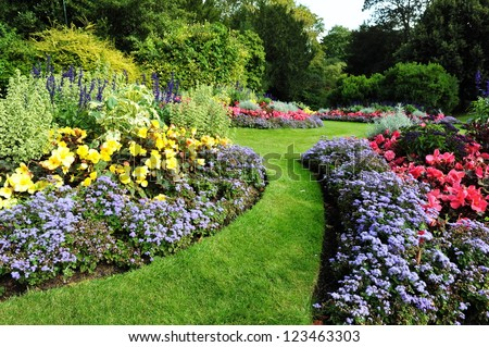 Colourful Flowerbeds and Winding Grass Pathway in an Attractive English Formal Garden #123463303
