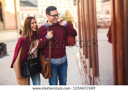 Beautiful young couple enjoying in shopping, walking and looking at store window. #1234637689