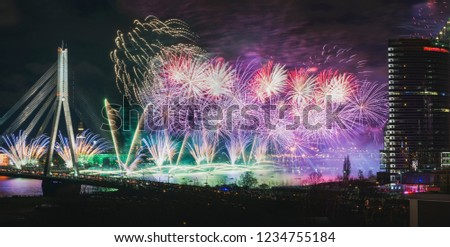 Colorful fireworks over river Daugava on Latvia's 100th birthday. Independence day celebration in Riga city with panoramic view over the old town and cable bridge. Light show in Riga city. #1234755184