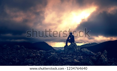 Dramatic Silhouette Of Man Sitting On Mountain Ridge Over Looking Stormy Skies #1234764640