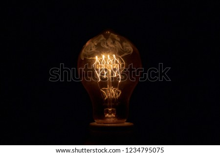 Bulb exploding with fire and  smoke . Slow capture exploding light bulb a dark background . #1234795075