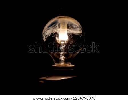 Bulb exploding with fire and  smoke . Slow capture exploding light bulb a dark background . #1234798078