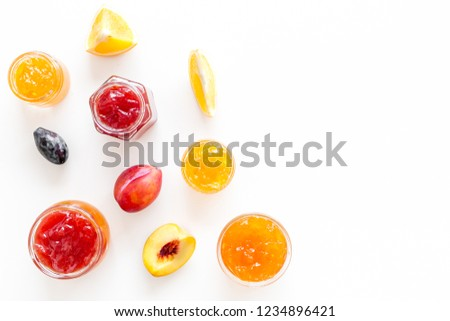 Jams different tastes made of fruits and berries near pieces of fruits on white background top view copy space #1234896421