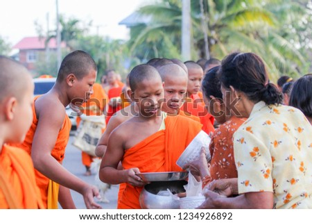 Buriram/Thailand - April 10, 2018: A group of novices morning alms round at villagage in Phatharin sub-district. #1234926892