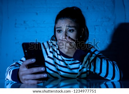 Frightened teenager or young woman using smart mobile cell phone as internet cyberbullying by message stalked abused victim. #1234977751