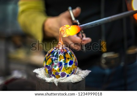 A Glass Blower Shaping Molten Glass into a Piece of Art #1234999018