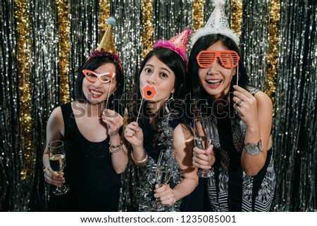 beautiful clubbing Asian women having fun at nightclub. young girls playing with funny fake glasses lips paper decoration face camera taking pictures. drunk crazy ladies with wine relax at night.
