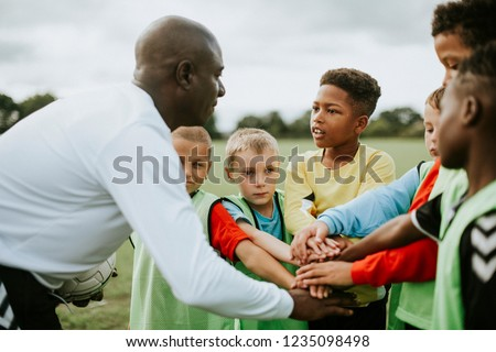 Junior football team stacking hands before a match Royalty-Free Stock Photo #1235098498