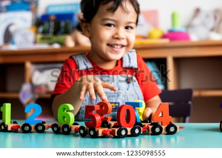 Little boy playing mathematics wooden toy at nursery #1235098555