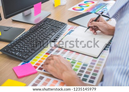 Image of male creative graphic designer working on color selection and drawing on graphics tablet at workplace with work tools and accessories in workspace. #1235145979