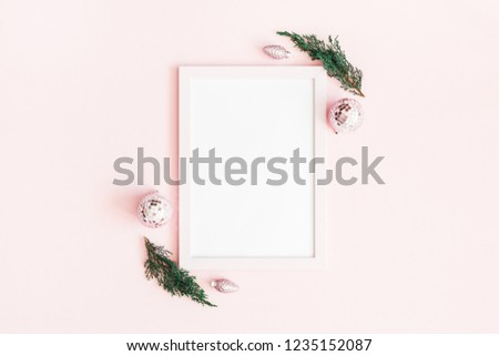 Christmas composition. Photo frame, pink decorations, fir tree branches on pastel pink background. Christmas, winter, new year concept. Flat lay, top view, copy space
