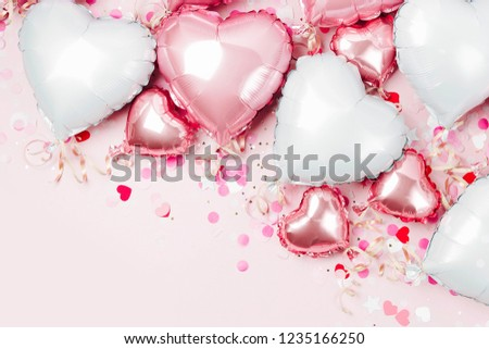 Air Balloons of heart shaped foil  on pastel pink background. Love concept. Holiday celebration. Valentine's Day or wedding/bachelorette party decoration. Metallic balloon #1235166250