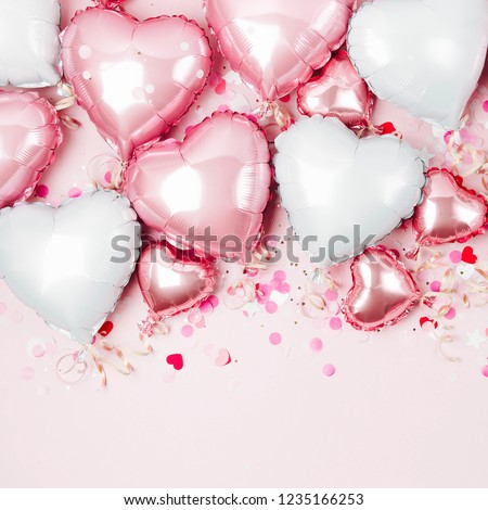 Air Balloons of heart shaped foil  on pastel pink background. Love concept. Holiday celebration. Valentine's Day or wedding/bachelorette party decoration. Metallic balloon #1235166253