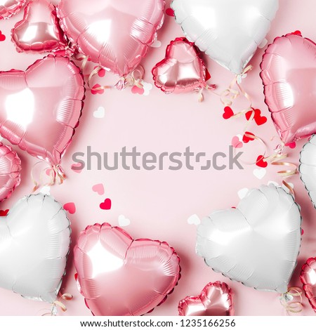 Air Balloons of heart shaped foil  on pastel pink background. Love concept. Holiday celebration. Valentine's Day or wedding/bachelorette party decoration. Metallic balloon #1235166256