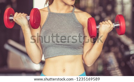 Time to hit the gym. Sportswoman working exercise for hands with weight. Close up. #1235169589