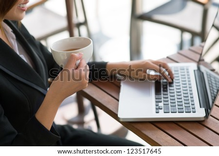 Positive business lady using her laptop and drinking tea #123517645