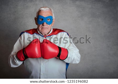 senior man with boxing gloves on gray background #1235196082