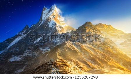 Hiker reaches the mountain peak of Machapuchare. A mountain in the Annapurna Himalayas of north central Nepal. View point from Mardi Himal base camp track #1235207290