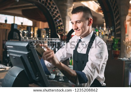 small business, people and service concept - happy man or waiter in apron at counter with cashbox working at bar or coffee shop #1235208862