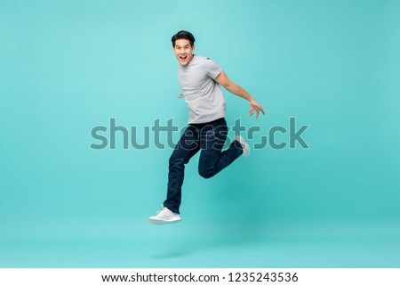 Energetic happy young Asian man in casual clothes jumping, studio shot isolated in light blue background #1235243536