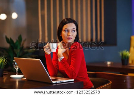 Beautiful young woman holding coffee in a cafe with a laptop on the table #1235252578