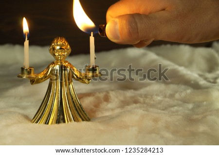 Bronze candlestick in the form of an angel                holding burning candles in his hands on dark wood and white artificial fur background. Man's hand igniting a candle lighter. #1235284213