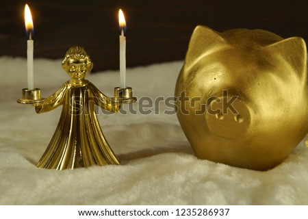 Bronze candlestick in the form of an angel                holding burning candles in his hands and a golden ceramic pig figure, on dark wood and white artificial fur background. Place for text / text. #1235286937