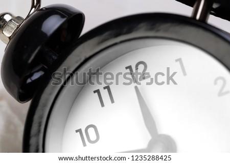 black vintage alarm clock on color background #1235288425
