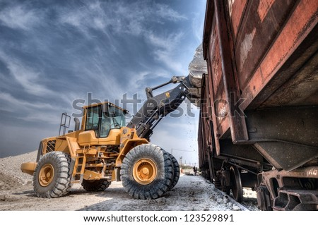 Wheel loader excavator with backhoe unloading clay Royalty-Free Stock Photo #123529891