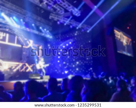 Abstract blurred concert with stage screen projecting male singer playing guitar, live performance background #1235299531