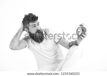 Hipster with beard and mustache overslept. Man with shocked face sits, holds alarm clock. Man needs to get up earlier, white background, copy space. Morning and overslept concept. #1235360221