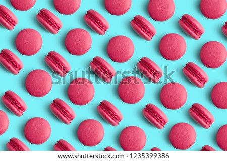 Macaroons on colored background, a pattern of colorful french cookies macarons. Beige, brown french cookies macarons on mint blue cyan background. Gift for Valentine's Day #1235399386
