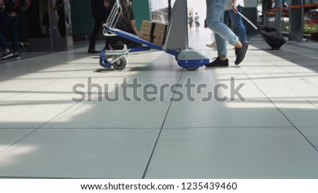 Unrecognizable people with baggages walking in terminal airport #1235439460