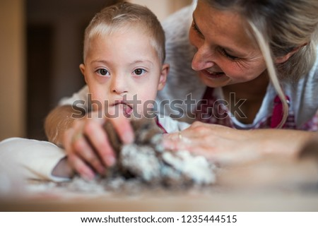 A happy handicapped down syndrome child with his mother indoors baking. #1235444515