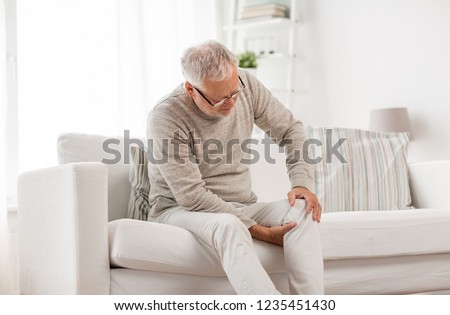 people, health care and problem concept - unhappy senior man suffering from knee ache at home #1235451430