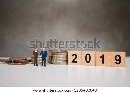 Miniature people, couple businessman standing with stack coins and year 2019 wooden block using as business concept #1235480848