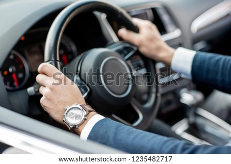 Close-up of businessman's hands on the helm of a luxury car #1235482717
