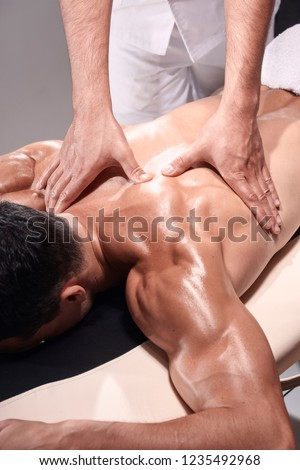 two young man, 20-29 years old, sports physiotherapy indoors in studio, photo shoot. Physiotherapist massaging muscular patient back side of shoulder or arm, with his hands close-up.