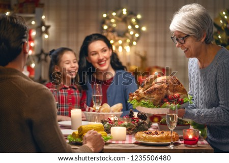 Merry Christmas! Happy family are having dinner at home. Celebration holiday and togetherness near tree. #1235506480