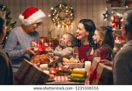 Merry Christmas! Happy family are having dinner at home. Celebration holiday and togetherness near tree. #1235506516