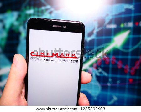 Murcia, Spain; Nov 19, 2018: Cinemark Theatres logo in phone with earnings graphic on background. Cinemark USA, Inc. (stylized as CineMark) is an American movie theatre chain #1235605603