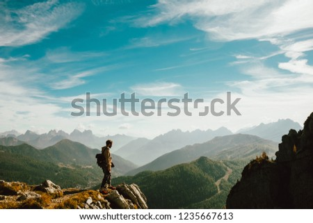 Belluno, Italy - 20 october 2018: - a young man standing over top of mountain canyon watches dramatic big valley extend in front of him making a step forward #1235667613