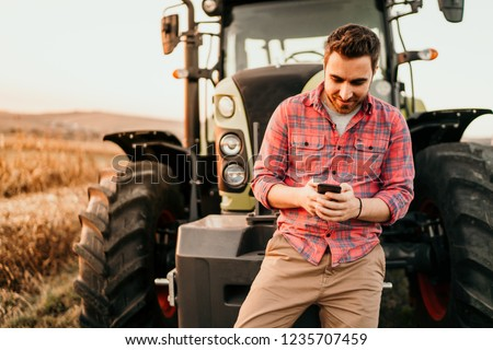 Portrait of smiling farmer using smartphone and tractor at harvesting. Modern agriculture with technology and machinery concept #1235707459