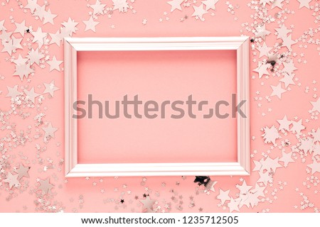 Festive elegant background. Blank photo frame on pastel pink background. Christmas, New Year, birthday concept. Flat lay, top view, copy space